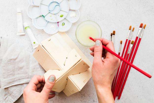 Una vista desde arriba de la mano de la mujer que pinta el modelo de casa de madera con pincel