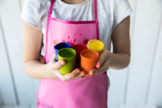 Una vista desde arriba de la mano de una niña sosteniendo muchas botellas de pintura de colores