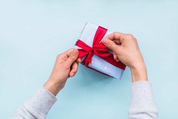 Vista de arriba de la mano que ata el arco de la cinta roja en la caja de regalo sobre fondo azul