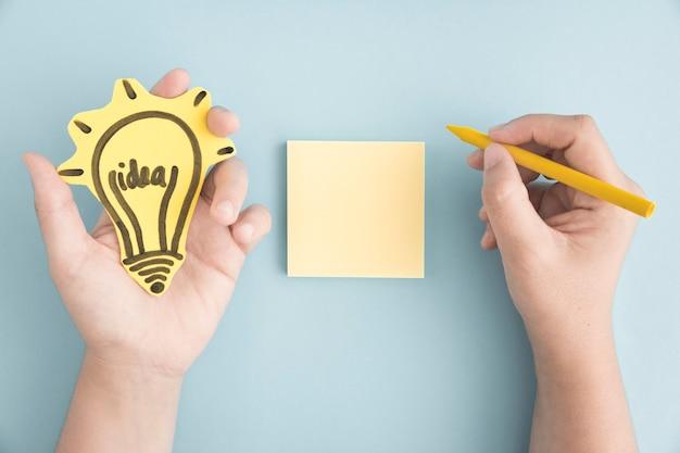 Vista de arriba de la mano que sostiene la escritura del bulbo de la idea con el crayón amarillo en nota adhesiva sobre el fondo gris
