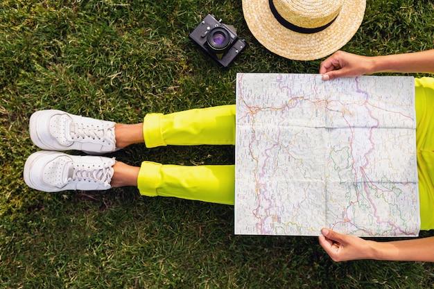 Vista desde arriba de las manos de la mujer negra sosteniendo el mapa, viajero con cámara divirtiéndose en el estilo de la moda de verano del parque, traje colorido hipster, sentado en la hierba, pantalones amarillos, piernas en calzado deportivo