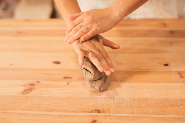 Una vista desde arriba de las manos de la mujer sobre la arcilla amasada en la mesa de madera