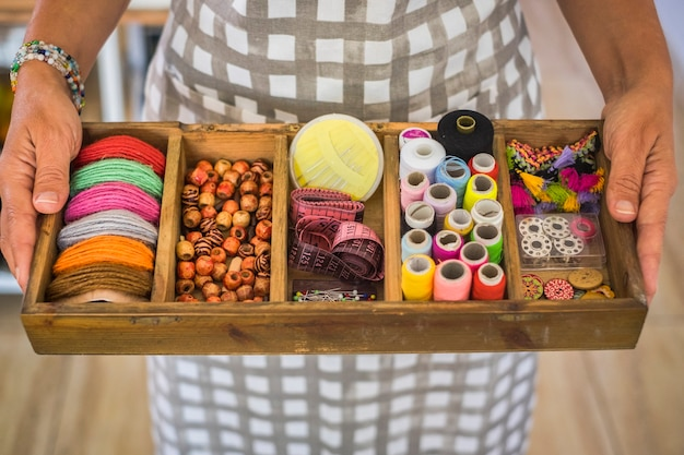 Vista desde arriba manos de mujer tomando una caja de madera llena de telas y artículos para que un sastre confeccione y repare ropa y vestidos.