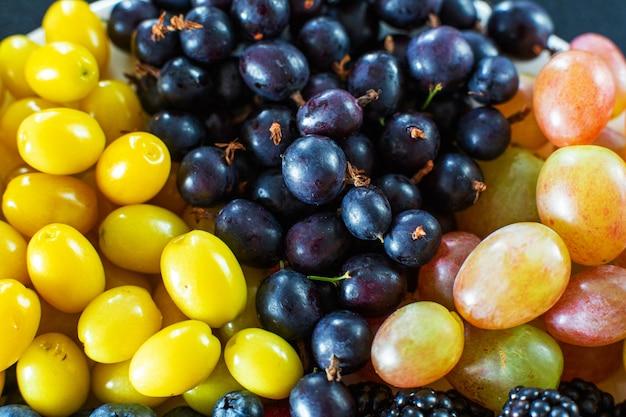 Vista desde arriba. mezcla de bayas en una terrel blanca. triángulo de separación. mezcla de frutas de verano. diseño elegante de bayas