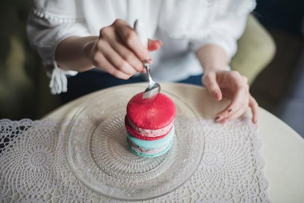 Una vista desde arriba de una mujer insertando la cuchara en un sándwich de helado en un plato sobre la mesa