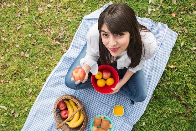 Una vista desde arriba de la mujer joven que muestra las frutas frescas en la mano