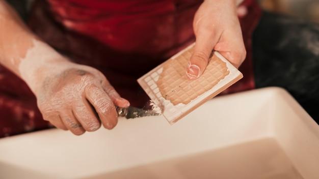 Una vista desde arriba de la mujer que quita la pintura con una herramienta afilada en azulejos