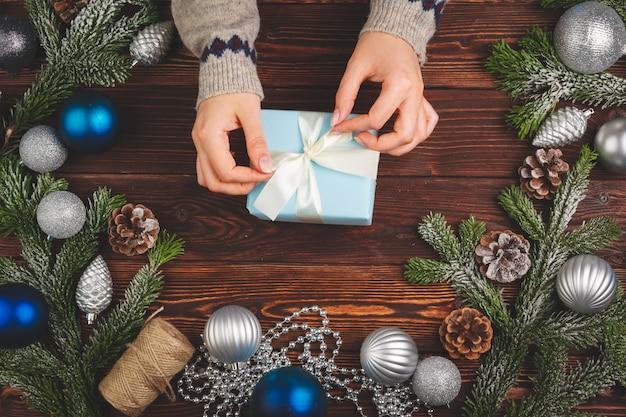 Vista desde arriba de mujer vistiendo suéter y sosteniendo un regalo decorado