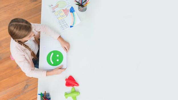 Una vista de arriba de la niña que sostiene la tarjeta feliz de los emoticons de la cara que se sienta en la oficina del psicólogo