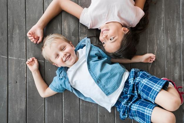 Una vista desde arriba del niño y la niña sonrientes acostado en el piso de madera dura