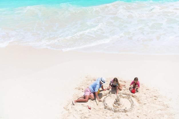 Vista desde arriba a padre e hijas pequeñas que hacen un castillo de arena en una playa tropical