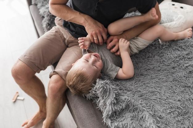 Una vista desde arriba del padre sentado en el sofá cosquillas a su hijo