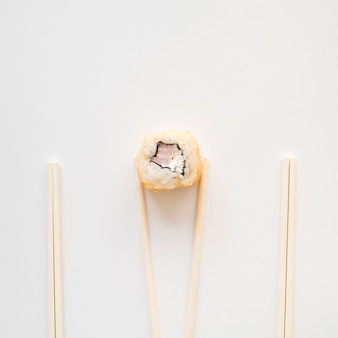 Vista desde arriba palillos sosteniendo un rollo de sushi