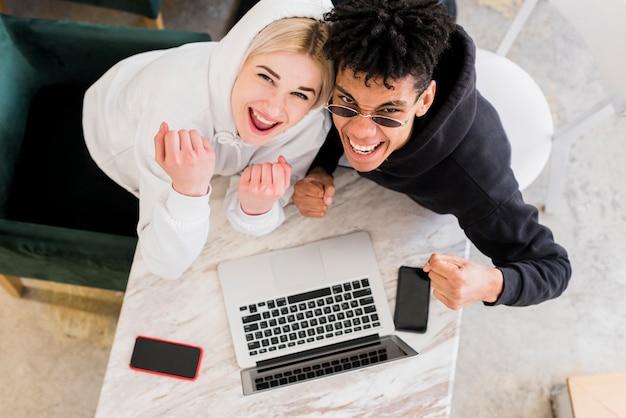 Una vista desde arriba de una pareja adolescente interracial apretando su puño mirando hacia arriba