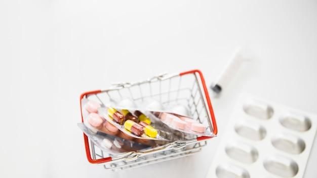Vista de arriba de las píldoras de ampolla en el carro de compras en el fondo blanco