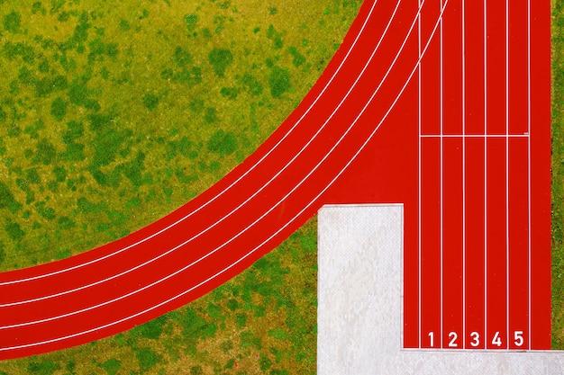 La vista desde arriba de las pistas de atletismo rojas comienzan con números y césped de hierba verde, pista de atletismo roja en el estadio, infraestructura para actividades deportivas