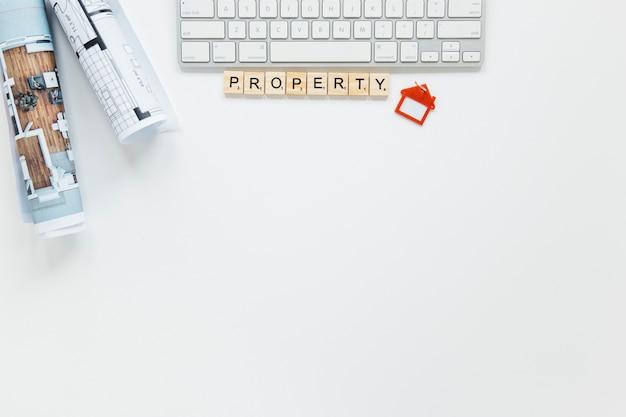 Vista de arriba del plano; teclado; bloque de propiedad y llavero de forma de casa con fondo copyspace