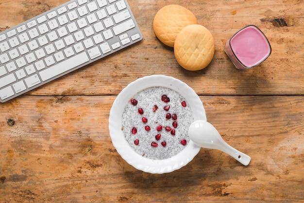Una vista desde arriba del pudín de semillas de chía; galletas; batido y teclado de computadora inalámbrico en la mesa