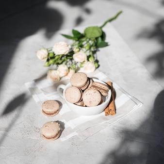 Una vista desde arriba del ramo de rosas con macarrones de canela en una taza blanca sobre fondo gris con textura de hormigón