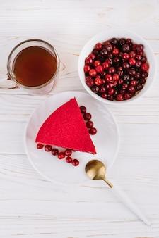 Una vista de arriba de la rebanada de la torta de la baya de la pasa roja en la placa blanca sobre el contexto texturizado de madera