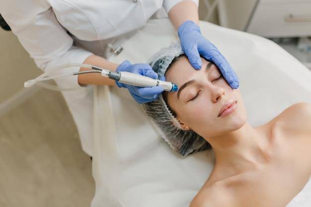 Vista desde arriba del rejuvenecimiento de hermosa mujer disfrutando de procedimientos de cosmetología en salón de belleza. dermatología, manos en resplandores azules, salud, terapia, botox