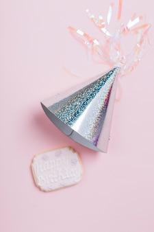 Vista de arriba del sombrero y de la galleta de plata del cumpleaños en fondo rosado