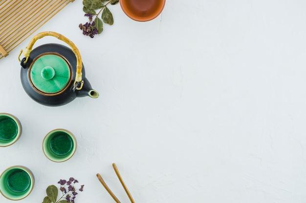 Una vista de arriba de la tetera y de las tazas herbarias verdes de cerámica con las hierbas aisladas en el fondo blanco