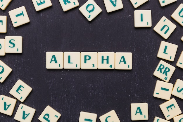 Vista de arriba del texto alfa en letras scrabble sobre fondo negro
