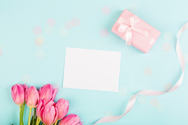 Vista desde arriba de tulipanes y caja de regalo con copia espacio en azul