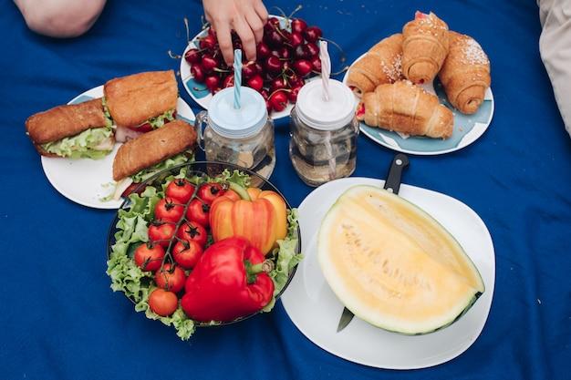 Vista desde arriba de verduras, frutas y sándwiches.