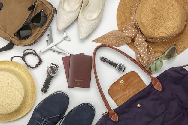 Vista de arriba del viaje accesorio y fondo del concepto de los hombres y de las mujeres de la moda. objetos de diferencia para el adulto o adolescente y viajero. artículos esenciales para el viaje en el escritorio de oficina blanco de madera en casa.