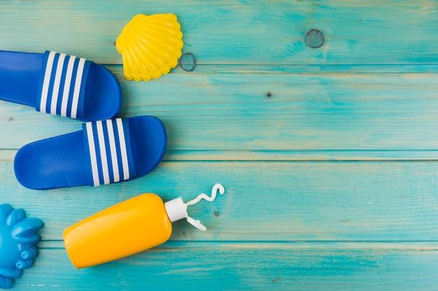 Una vista desde arriba de la vieira de plástico amarillo; chanclas y botella de loción de protección solar sobre fondo de madera turquesa