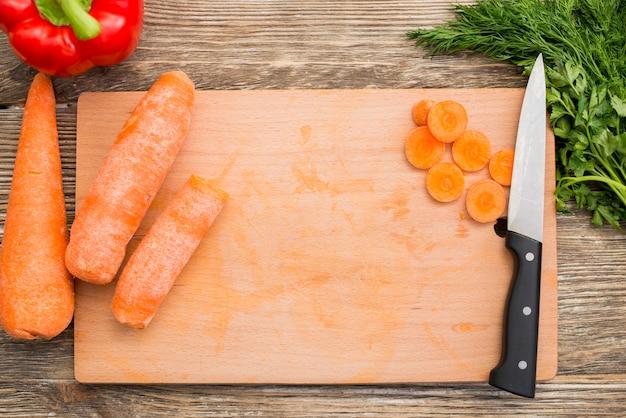 Una vista desde arriba de la zanahoria; pimiento rojo; perejil en el escritorio de madera
