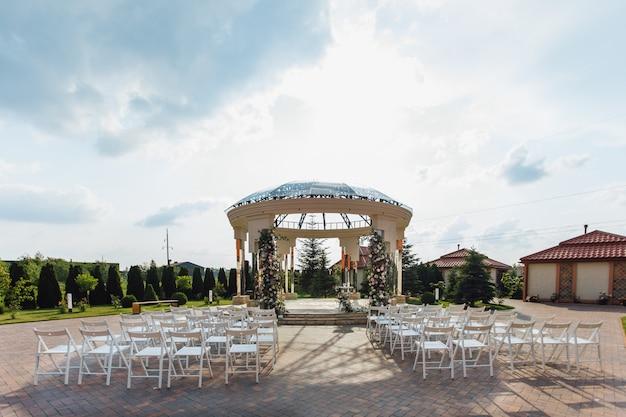 Vista de los asientos para invitados y el arco de bodas ceremoniales en la soleada plaza