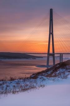 Vista del atardecer de invierno con nieve fresca y largo puente atirantado en vladivostok, rusia