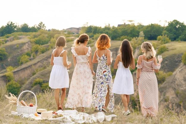 Vista desde atrás. la compañía de hermosas amigas disfruta de un paisaje veraniego verde y bebe alcohol. concepto de personas
