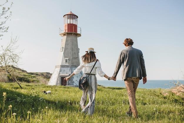Vista desde atrás en estilo indie hipster pareja joven enamorado caminando en el campo, tomados de la mano, faro en el fondo, día cálido de verano, soleado, traje bohemio, sombrero