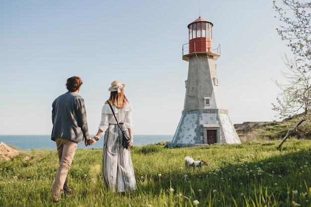 Vista desde atrás en estilo indie hipster pareja joven enamorado caminando en el campo, tomados de la mano