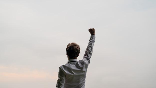 Vista desde atrás de un exitoso joven empresario de pie bajo el cielo
