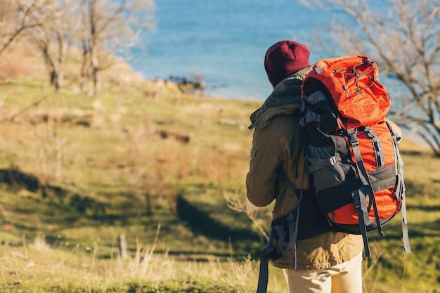 Vista desde atrás en hipster hombre viajando con mochila con chaqueta y sombrero, turista activo, usando teléfono móvil, explorando la naturaleza en la estación fría