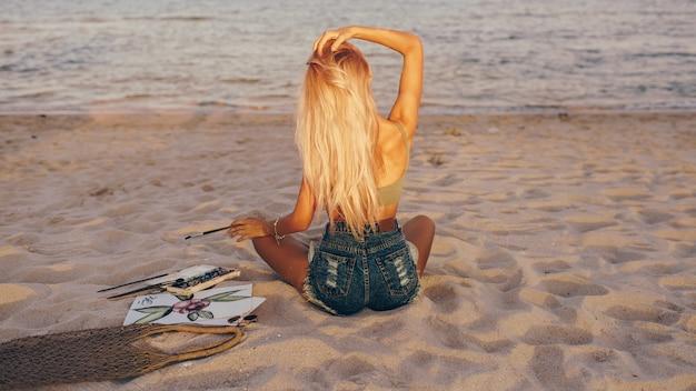 Vista desde atrás de una mujer rubia con pincel mirando el mar, mientras dibuja una imagen de acuarela