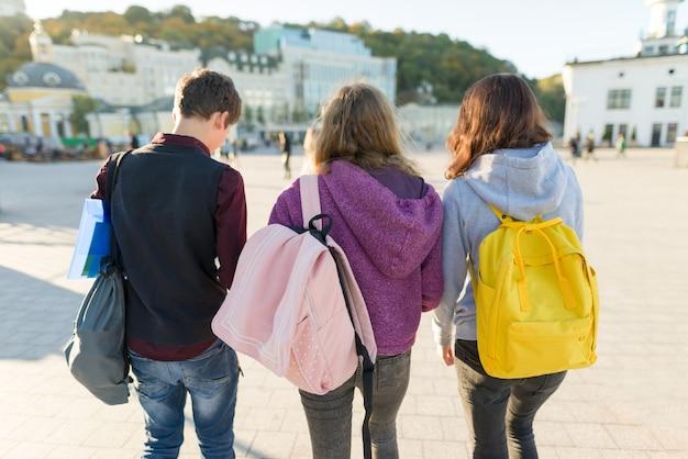 Vista desde atrás de tres estudiantes de secundaria con mochilas