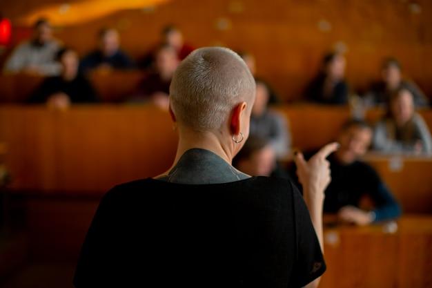 Vista de la audiencia de estudiantes detrás de una maestra