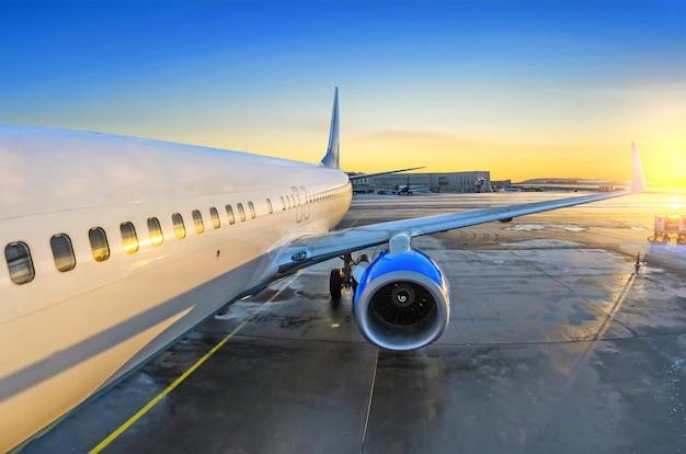 Vista del avión del pasajero en la entrada, salida del sol y estacionamiento en el motor del aeropuerto