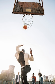 Vista baja amigos jugando baloncesto al aire libre