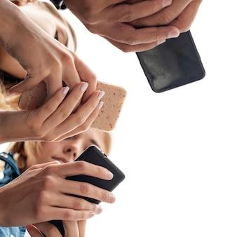 Vista baja de amigos navegando por teléfonos