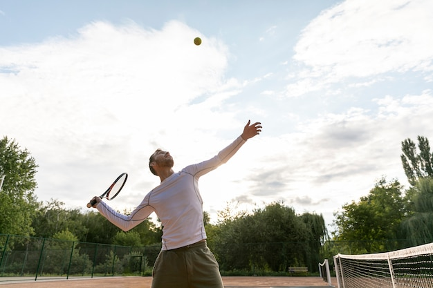 Vista baja hombre sirviendo durante el partido de tenis