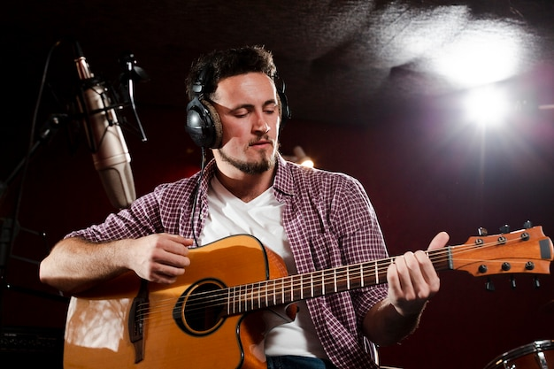 Vista baja de un hombre tocando la guitarra y con los auriculares puestos
