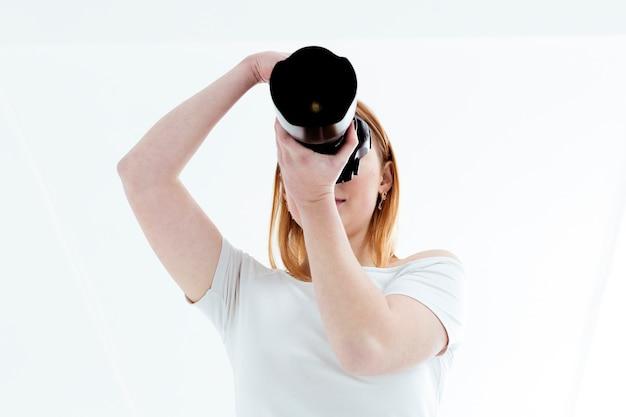 Vista baja de mujer tomando una foto con cámara profesional