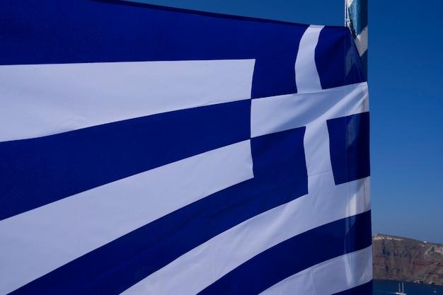 Vista de la bandera griega en el viento, oia, santorini, grecia